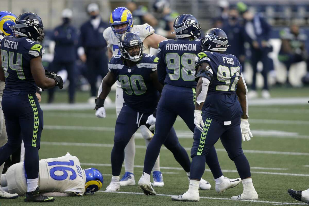 Seattle Seahawks defensive end Alton Robinson (98) reacts with teammates after he sacked Los Angeles Rams quarterback Jared Goff (16) during the second half of an NFL football game, Sunday, Dec. 27, 2020, in Seattle. (AP Photo/Scott Eklund)