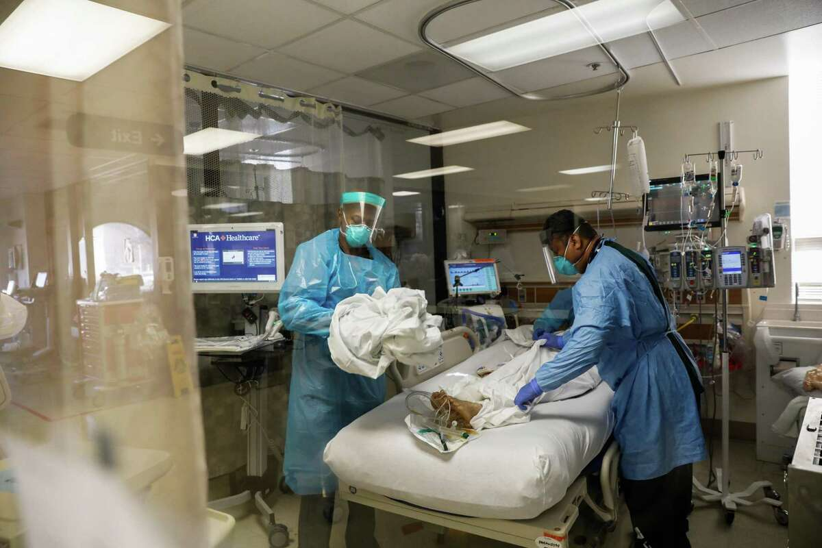 Nurses Waymond Jones (left) and Larry Ngiraswei work with a COVID-19 patient in the intensive care unit at Regional Medical Center in San Jose. The center has canceled nonurgent surgeries amid the surge.