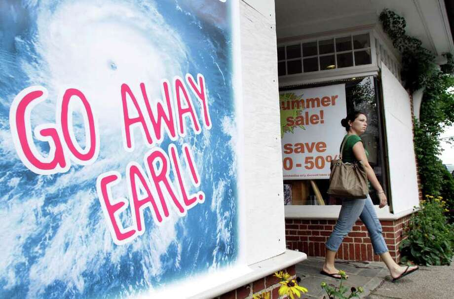 A passer-by walks past a store-front window featuring a placard depicting Hurricane Earl, in Chatham, Mass., Friday, Sept. 3, 2010. Some shops in the town have boarded their windows in anticipation of the storm. (AP Photo/Steven Senne) Photo: Steven Senne