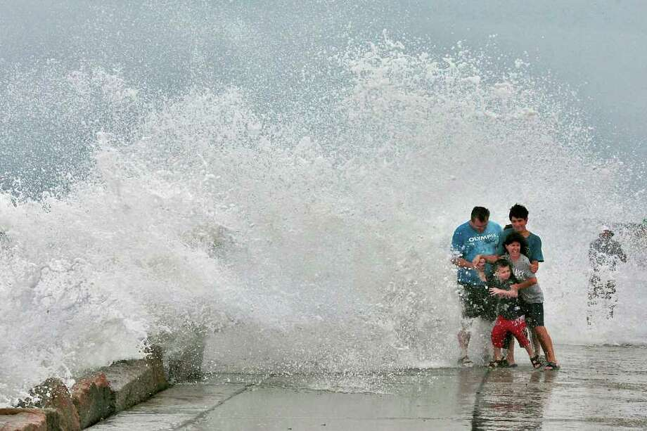The Gallishaw family from Seekonk, Mass., braces for a large wave as it crashes over the Goosebury Island causeway in Westport, Mass., as Hurricane Earl approaches Friday, Sept. 3, 2010. (AP Photo/Standard Times , Peter Pereira) Photo: Peter Pereira