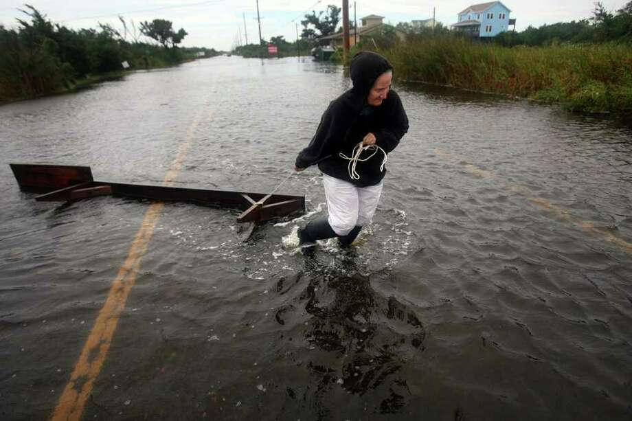 Kim Harper drags a workbench back to her home across flooded Hwy 12  in Frisco, N.C. Friday, Sept. 3, 2010 after sound side flood waters from Hurricane Earl carried it away overnight. (AP Photo/The Virginian-Pilot, Steve Early) Photo: Steve Early
