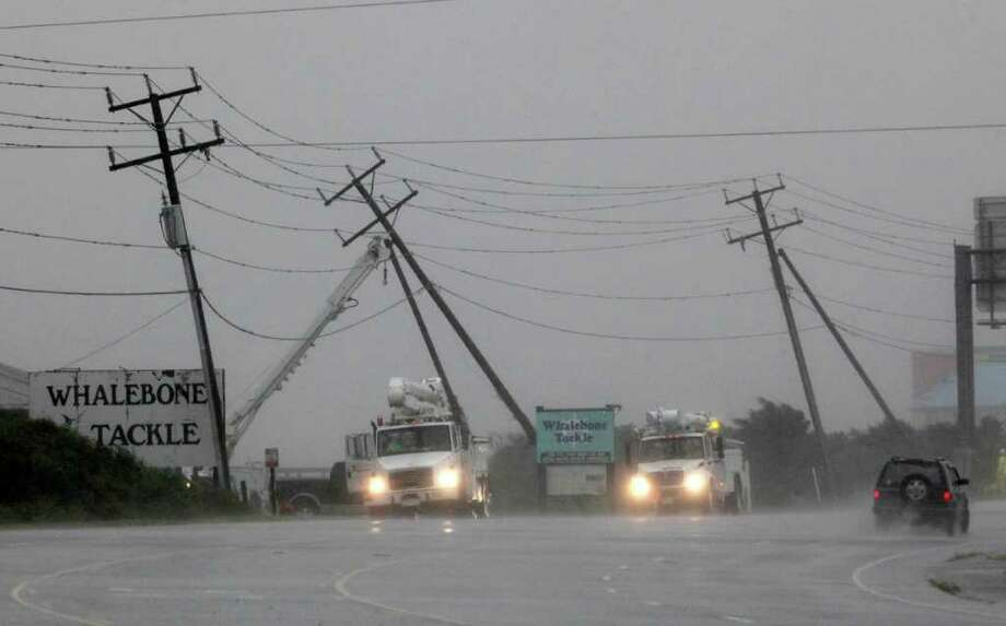 Utilities workers try to support power lines that were blown sideways from winds produced by Hurricane Earl in Nags Head, N.C., Friday, Sept. 3, 2010. (AP Photo/Gerry Broome) Photo: Gerry Broome / AP
