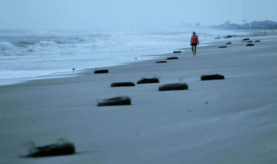 A woman walks on the beach past tires washed up after Hurricane Earl brushed the North Carolina coast in Atlantic Beach, N.C., Friday, Sept. 3, 2010. (AP Photo/Chuck Burton) Photo: Chuck Burton