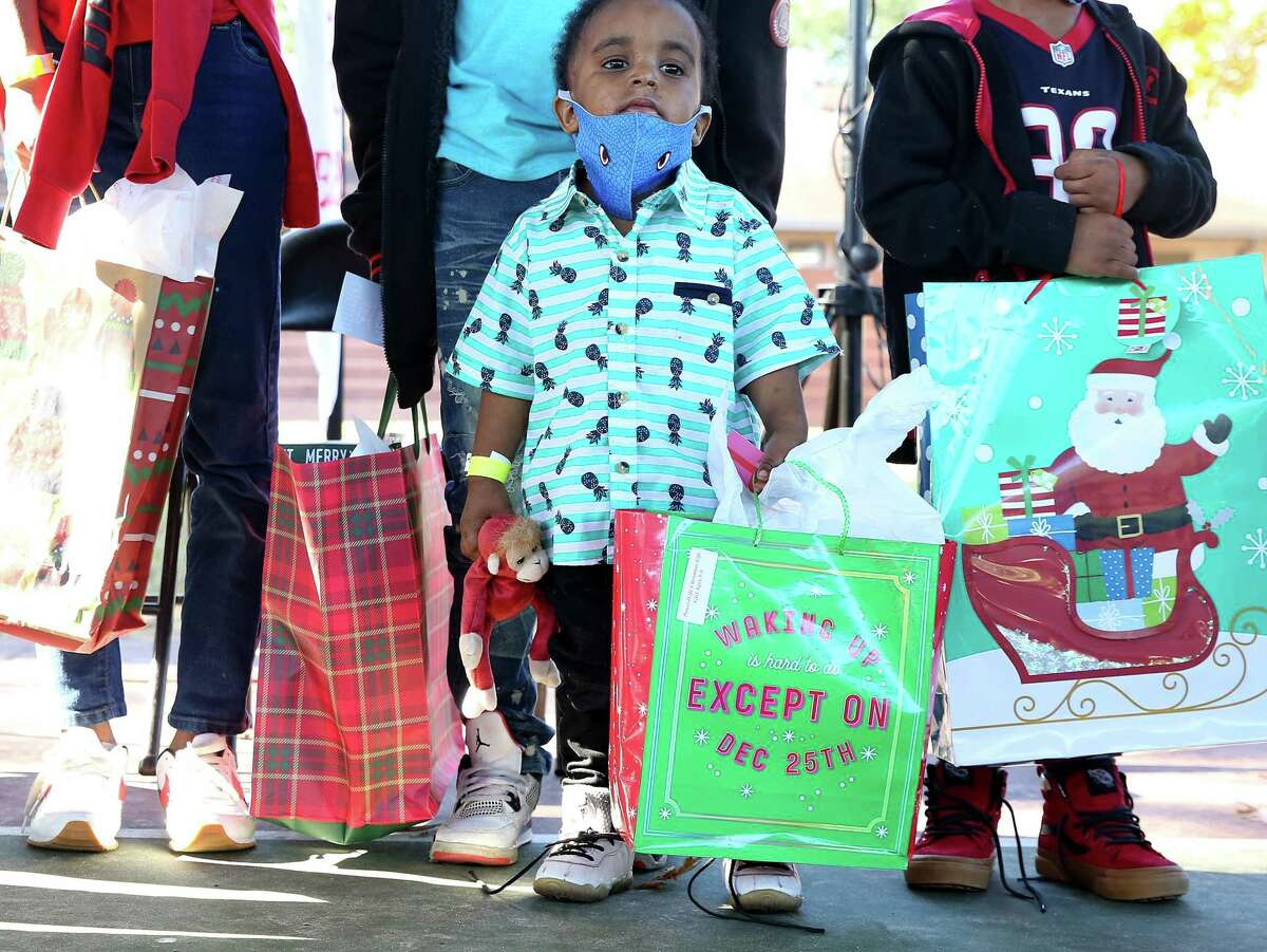 Jordan Smith, 2, poses for a photo with his siblings after getting some Christmas gifts Sunday at Cuney Home Apartments in Houston. Kids Lives matter partnered with The Deshaun Watson Foundation to pass out gifts, food and clothing to over 500 families.