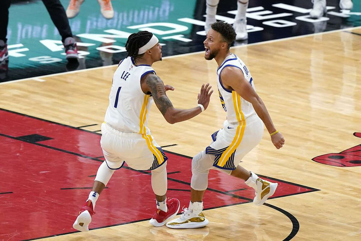 Golden State Warriors guard Damion Lee, left, celebrates with Stephen Curry after making the game-winning 3-pointer against the Bulls on Dec. 27/