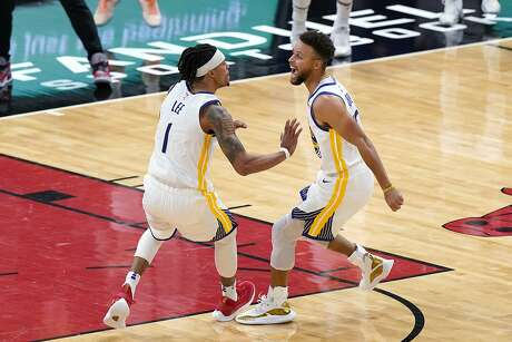 Golden State Warriors guard Damion Lee, left, celebrates with Stephen Curry after making the game-winning 3-point basket during the second half of an NBA basketball game against the Chicago Bulls in Chicago, Sunday, Dec. 27, 2020.  (AP Photo/Nam Y. Huh)