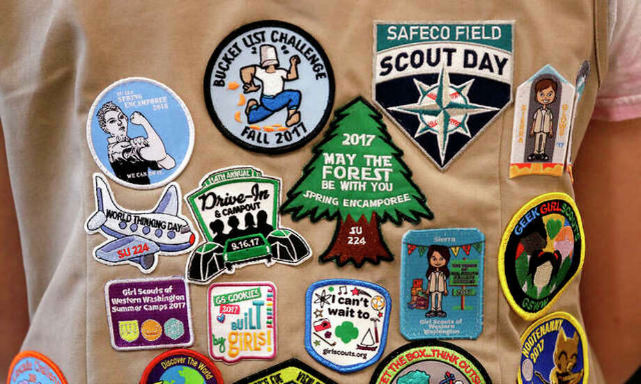 """Patches cover the back of a Girl Scout's vest at a demonstration of some of their activities. Girl Scouts of the United States of America claim the century-old organization is in a """"highly damaging"""" recruitment war with Boy Scouts of America after the group opened its core services to girls, leading to marketplace confusion and some girls unwittingly joining the Boy Scouts. Photo: Elaine Thompson 
