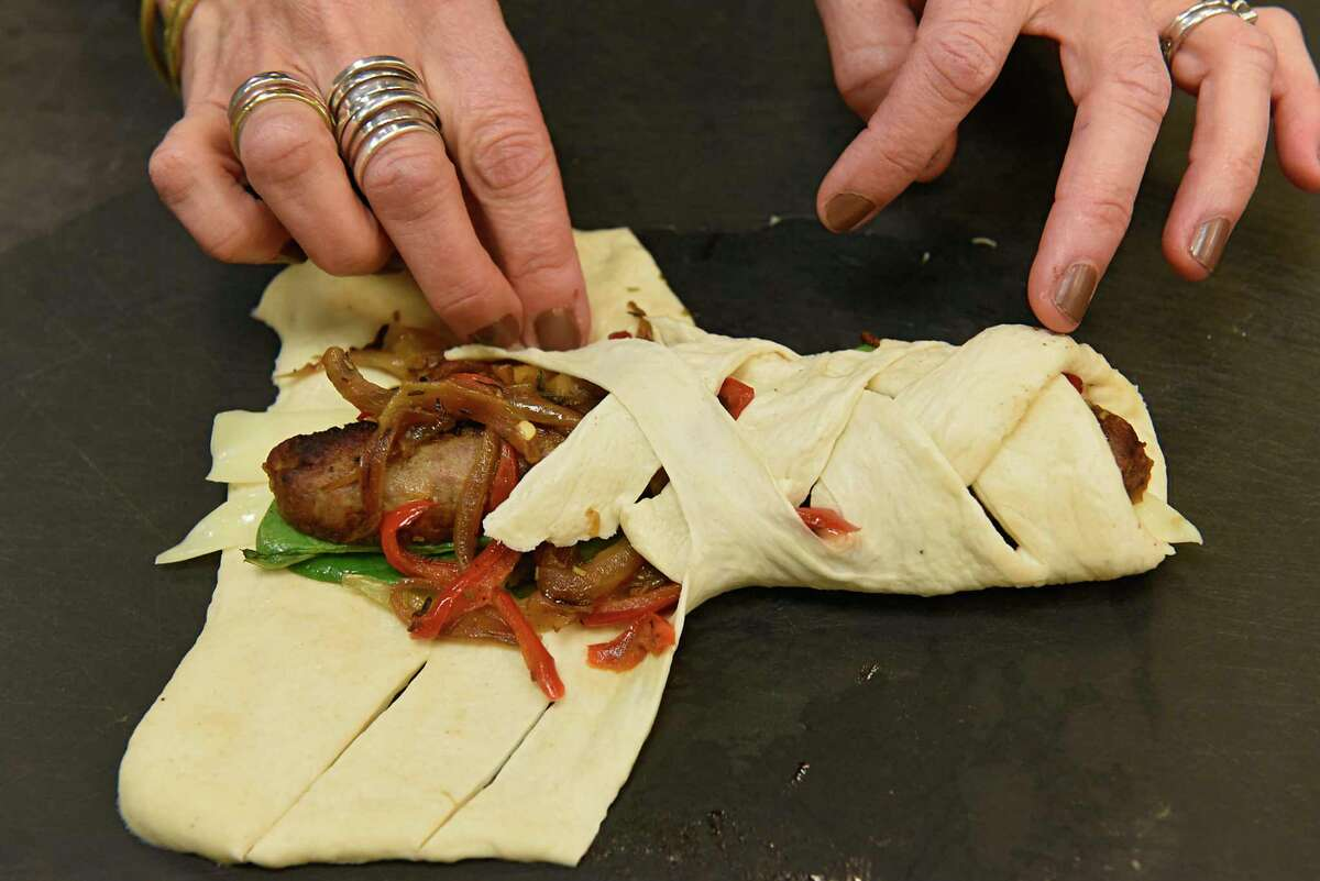 Caroline Barrett prepares sausage stromboli with provolone, veggies and herbs at Different Drummer's Kitchen in Stuyvesant Plaza on Wednesday, Dec. 23, 2020 in Albany, N.Y. (Lori Van Buren/Times Union)