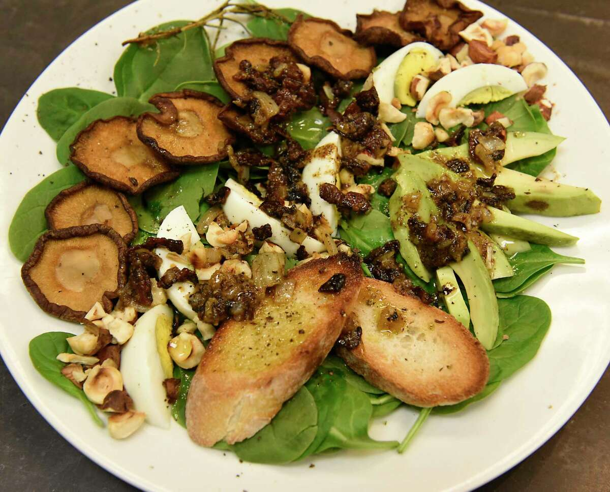 Crispy shiitake spinach salad with warm bacon dressing Caroline Barrett prepared at Different Drummer's Kitchen in Stuyvesant Plaza on Wednesday, Dec. 23, 2020 in Albany, N.Y. (Lori Van Buren/Times Union)