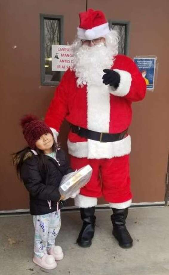 "Santa gives a gift to a ""good girl,"" three-year-old Lizbeth Rodriguez, daughter of Patricia Herrera."