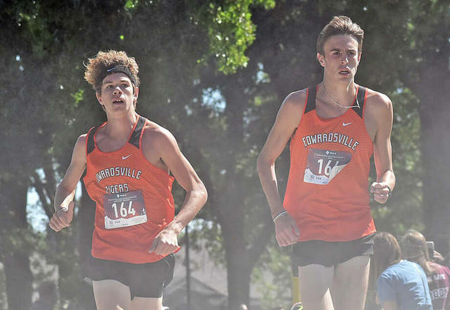Edwardsville's Geordan Patrylak, left, and Ryan Watts run through a cloud of dust from the pace cart during the Granite City Invitational on Saturday. Watts won the race in 15:00.34 and Patrylak took third in 15:38.39. Photo: Matt Kamp|The Intelligencer