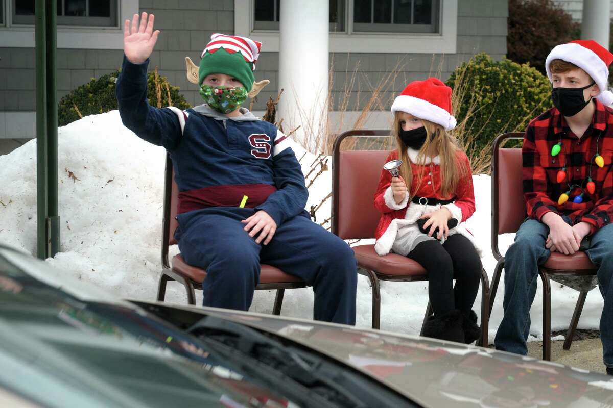From left, young volunteers Tyler Kudey, Gracie Dumas and Joey Dumas greet seniors during a curbside holiday meal pickup in front the Shelton Senior Center, in Shelton, Conn. Dec. 24, 2020.