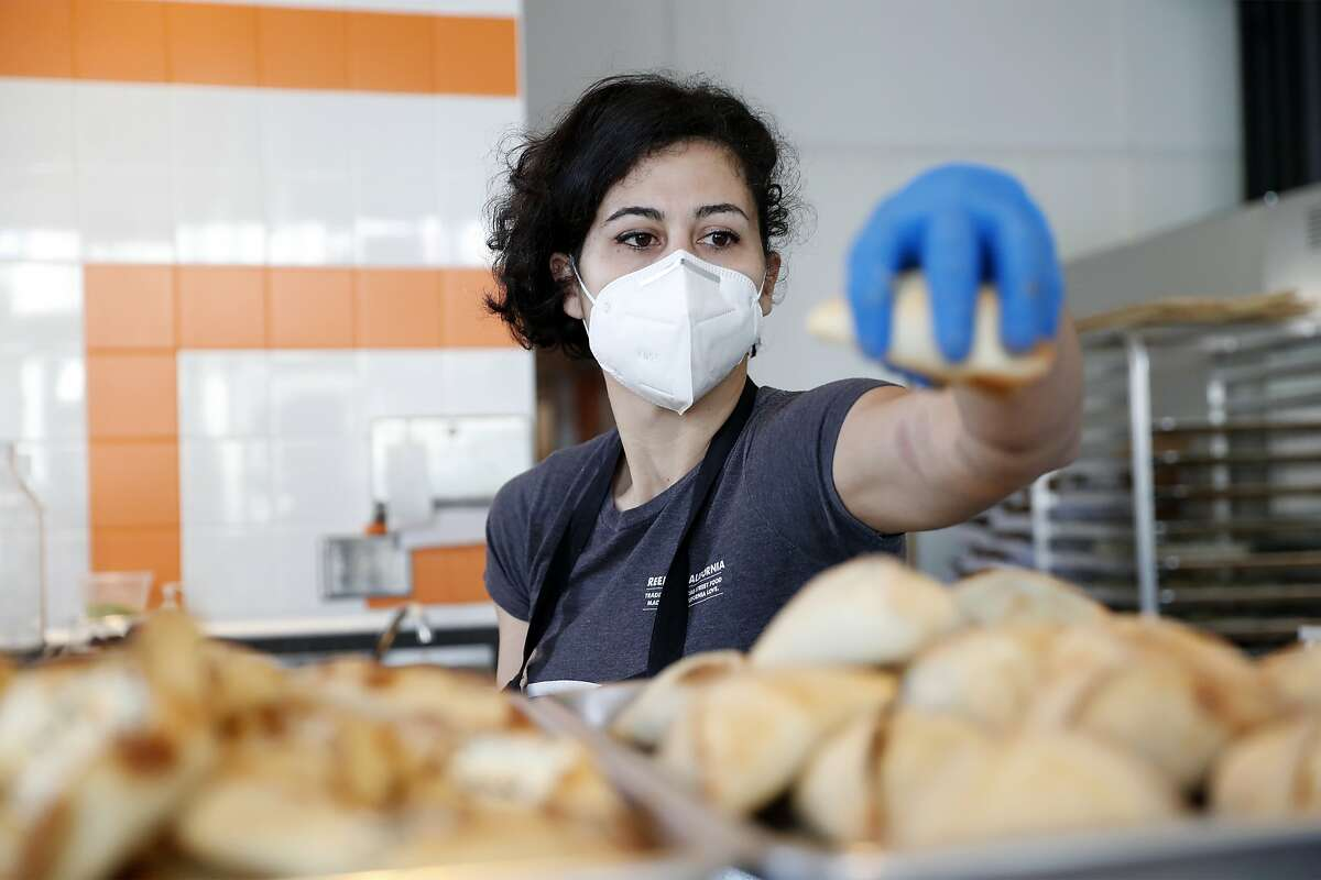 Chef and owner Reem Assil places turnovers on a tray at Reem's California on Mission Street in San Francisco, California.