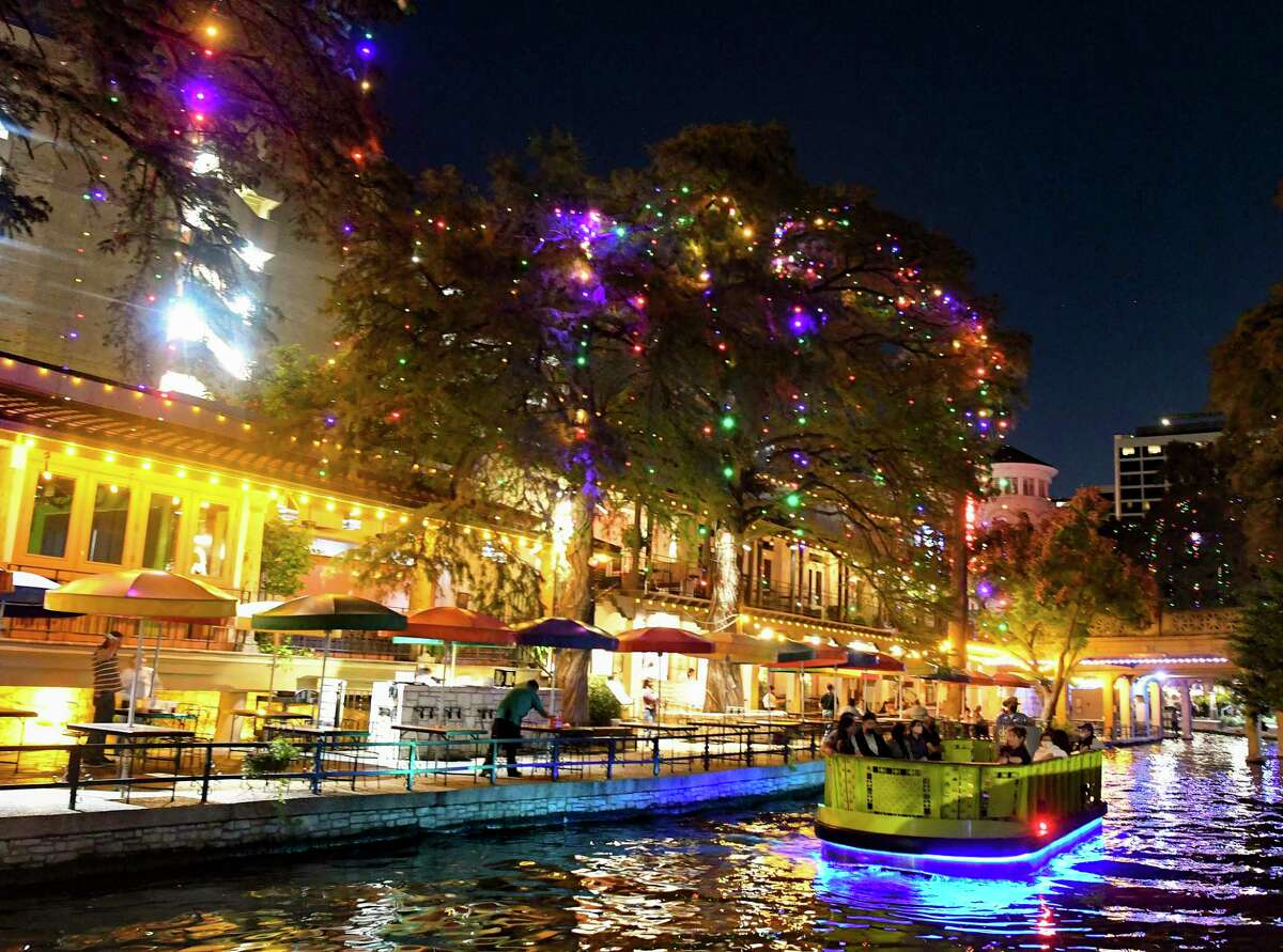 The River Walk Christmas lights shine after being turned on after a countdown by Mayor Ron Nirenberg from his home, where is in Covid-19 quarantine, on Thursday, Nov. 12, 2020. The 100,000 lights hang from the bald cypress trees that line the River Walk. The lights will shine through Jan. 4, 2021.