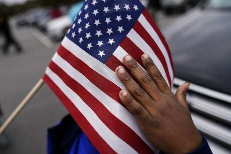 FILE - In this Nov. 15, 2020, fie photo a young child holds an American flag as Georgia Democratic candidate for U.S. Senate Raphael Warnock speaks during a campaign rally in Marietta, Ga. (AP Photo/Brynn Anderson, File)
