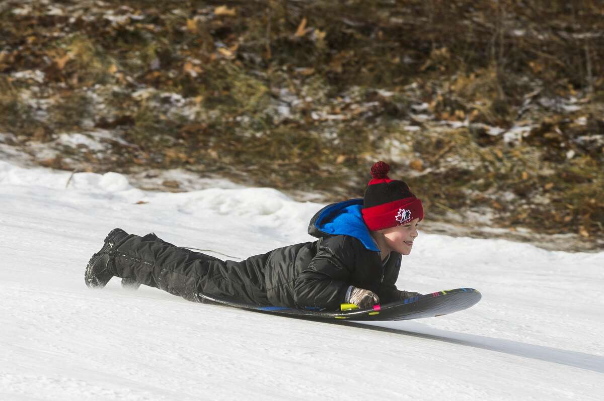 Children and their families enjoy a day of sledding Monday, Dec. 28, 2020 at the City Forest sledding hill in Midland. (Katy Kildee/kkildee@mdn.net)