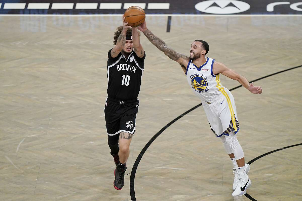 Golden State Warriors guard Mychal Mulder (15) defends against a pass by Brooklyn Nets guard Tyler Johnson (10) during the second half of an opening night NBA basketball game, Tuesday, Dec. 22, 2020, in New York. (AP Photo/Kathy Willens)