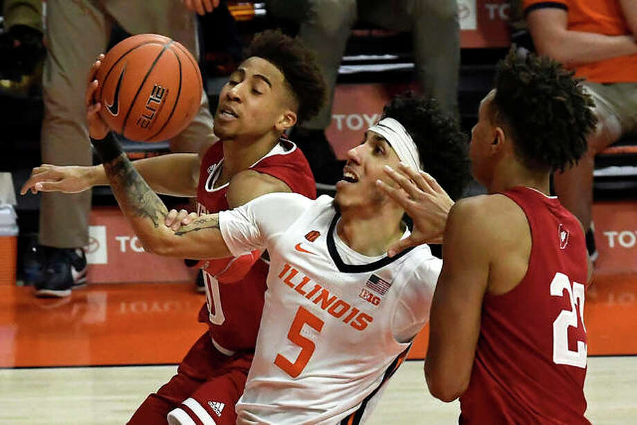 Illinois' Andre Curbelo (5) goes to the rim between Indiana's Rob Phinisee and Trayce Jackson-Davis (right) during the first half of a Big Ten Conference men's basketball game Saturday in Champaign. Photo: Associated Press