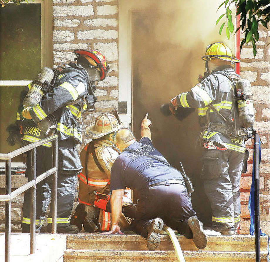 A photo from early in the progression of a fire shows assistant chiefs confering on strategy as smoke billows up from the fire in the building adjacent to the sanctuary at St. Paul's Episcopal Church.