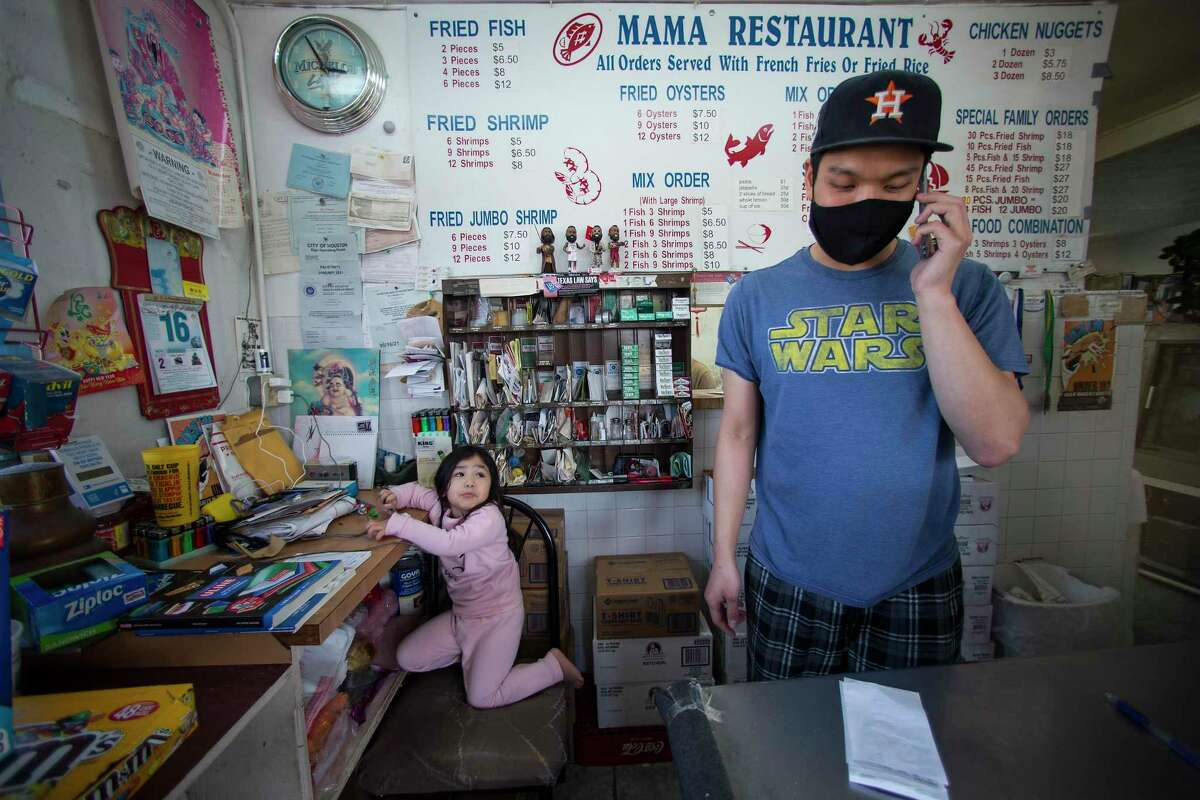Tommy Huynh takes an order at the front counter of his family's restaurant, Mama Seafood, Wednesday, Dec. 16, 2020 in Houston. The family-run restaurant at Parker at Jensen is located where the city's troubled sewer system has particular problems during heavy rains. Several times a year, rains force raw sewage out of the drain in the middle of the restaurant's kitchen floor.