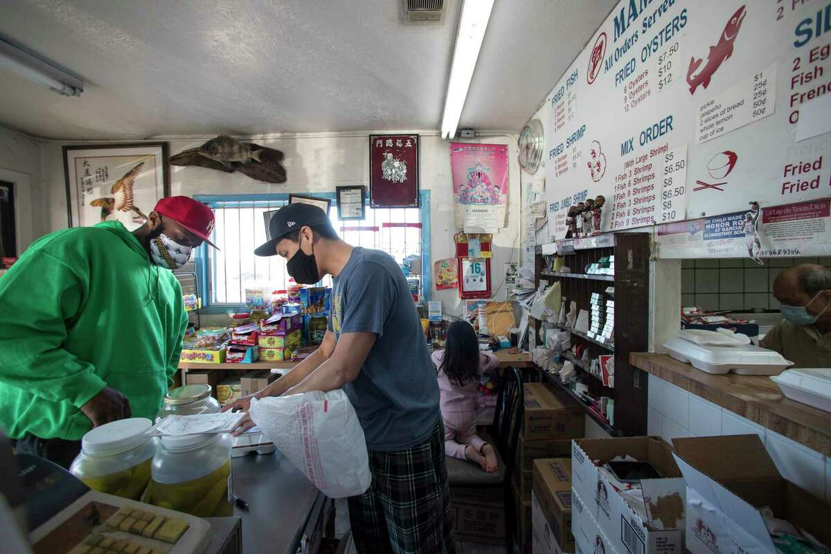 Tommy Huynh takes an order at the front counter of his family's restaurant, Mama Seafood, Wednesday, Dec. 16, 2020 in Houston.