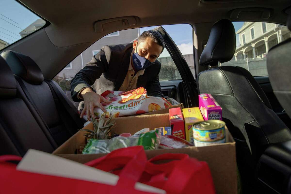 STAMFORD, CONNECTICUT - DECEMBER 22: Community health worker Luis Hernandez delivers groceries to families with COVID-19 on December 22, 2020 in Stamford, Connecticut. The non-profit Family Centers and the Stamford Department of Health are working with residents and their families who have tested positive, are quarantined and/or referred through testing sites. Funded by a grant from the Connecticut Health Foundation, the Community Health Worker Initiative also connects residents, particularly those from low-income communities, with additional resources and support services to manage their health and the wellbeing of their families during the pandemic. (Photo by John Moore/Getty Images)