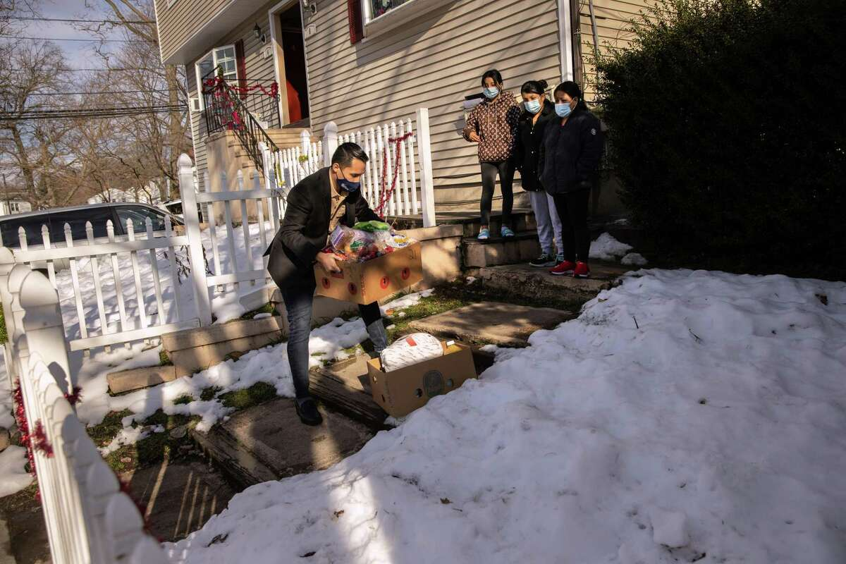 STAMFORD, CONNECTICUT - DECEMBER 22: Community health worker Luis Hernandez delivers groceries to a family with COVID-19 on December 22, 2020 in Stamford, Connecticut. The non-profit Family Centers and the Stamford Department of Health are working with residents and their families who have tested positive, are quarantined and/or referred through testing sites. Funded by a grant from the Connecticut Health Foundation, the Community Health Worker Initiative connects residents, particularly those from low-income communities, with additional resources and support services to manage their health and the wellbeing of their families during the pandemic. (Photo by John Moore/Getty Images)