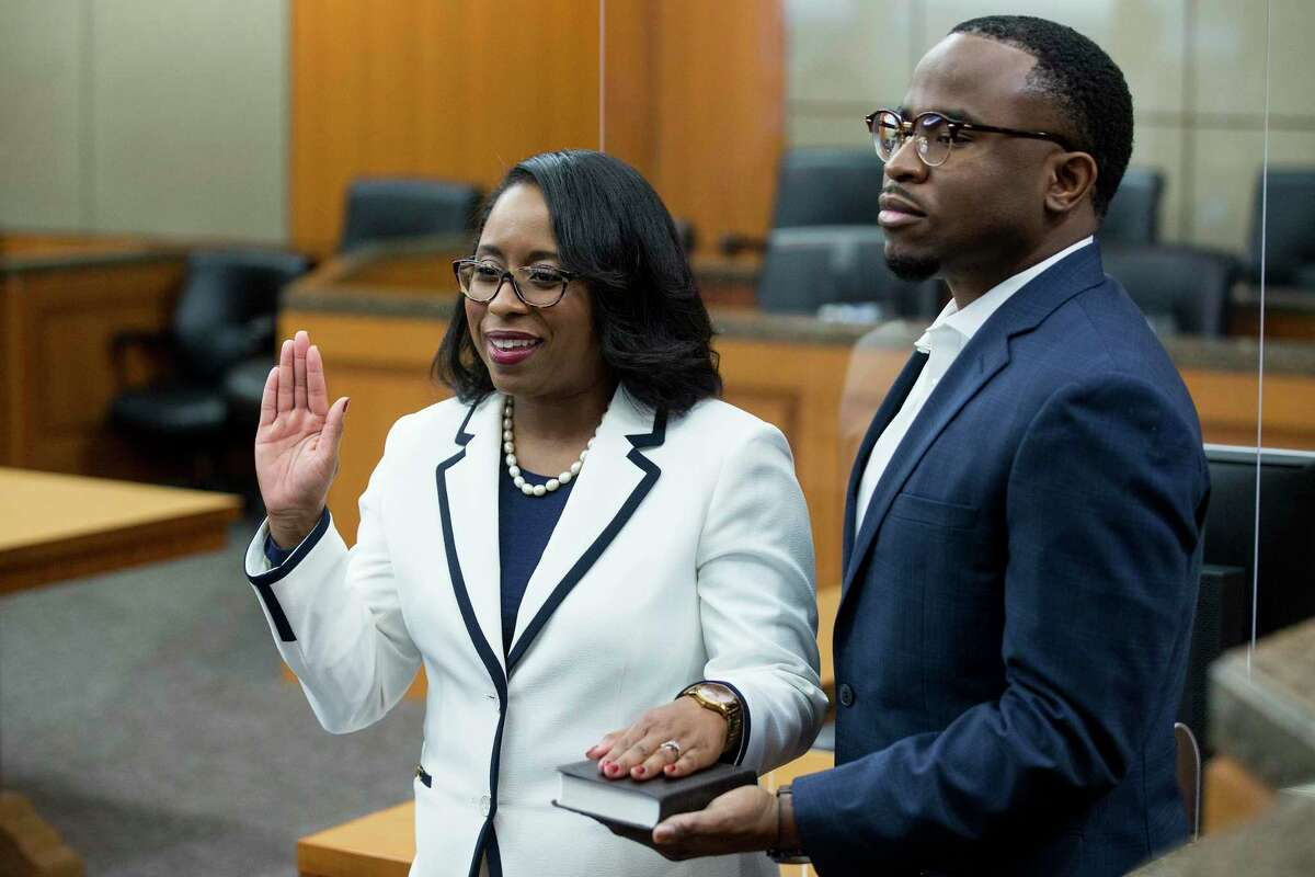 Texas Southern University alumna Teneshia Hudspeth stands with her husband, Samson Babalola, as she is sworn in as the new Harris County Clerk, by Judge Lesley Briones Tuesday, Nov. 17, 2020 in Houston.