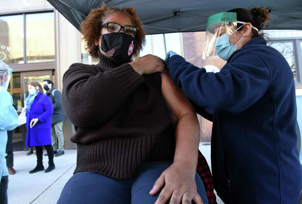 Dr. Tamiko Jackson-McArthur, left, gets the first dose of a Moderna COVID-19 vaccine from New Haven Public Health nurse Kara Delvecchio in front of the New Haven Health Department on Dec. 28, 2020.