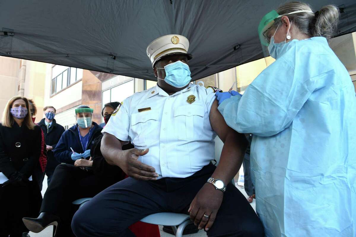 New Haven Fire Department Chief John Alston Jr., gets the first dose of a Moderna COVID-19 vaccine from APRN Grace Grajales in front of the New Haven Health Department on Dec. 28, 2020.