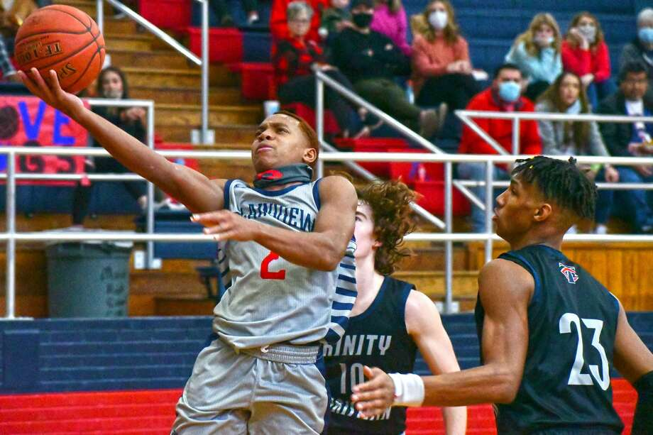 Plainview's Karomo Collins glides past a pair of Lubbock Trinity Christian defenders for the bucket during their non-district boys basketball game on Monday in the Dog House at Plainview High School. Photo: Nathan Giese/Planview Herald