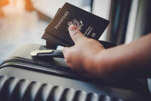 Cropped Hand Holding Passport And Luggage