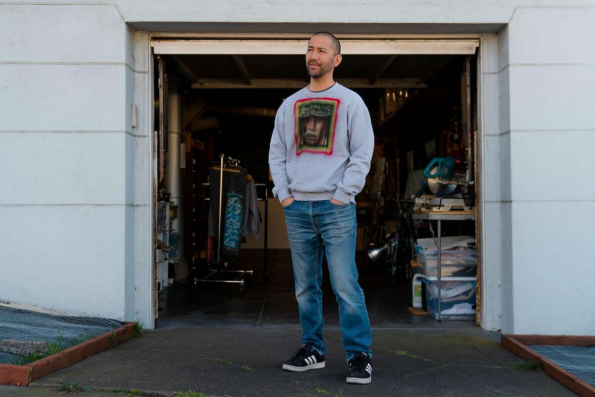 Nathan Tan poses for a photo outside the garage studio where he paints and operates his apparel brand, New Skool, in San Francisco, Calif., on Tuesday, December 22, 2020.