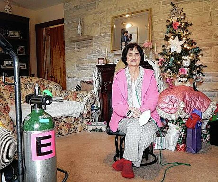 Karla Henderson sits in the living room of her Jacksonville home, an oxygen tank nearby, as she recovers from a bout of COVID-19 that put her in the hospital for two weeks. Photo: Angela Bauer | Journal-Courier