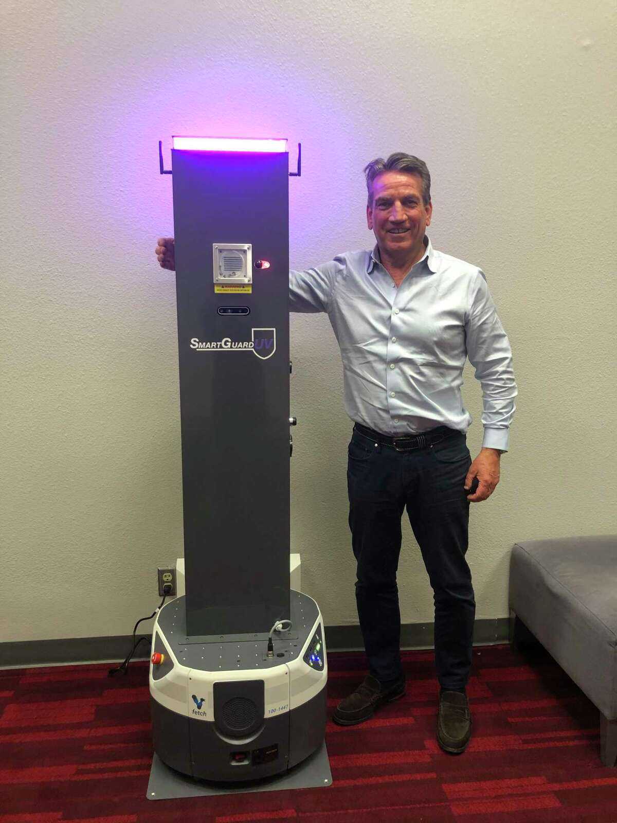Bill Butler, CEO of SmargGuardUV, with the company's autonomous mobile robot