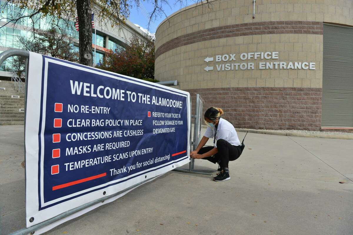 Amanda Caudillo, parking supervisor of the AlamoDome, puts up signage prior to a media tour of the Alamodome Monday afternoon to demonstrate the Covid-19 safety protocols that are in place for the Valero Alamo Bowl.