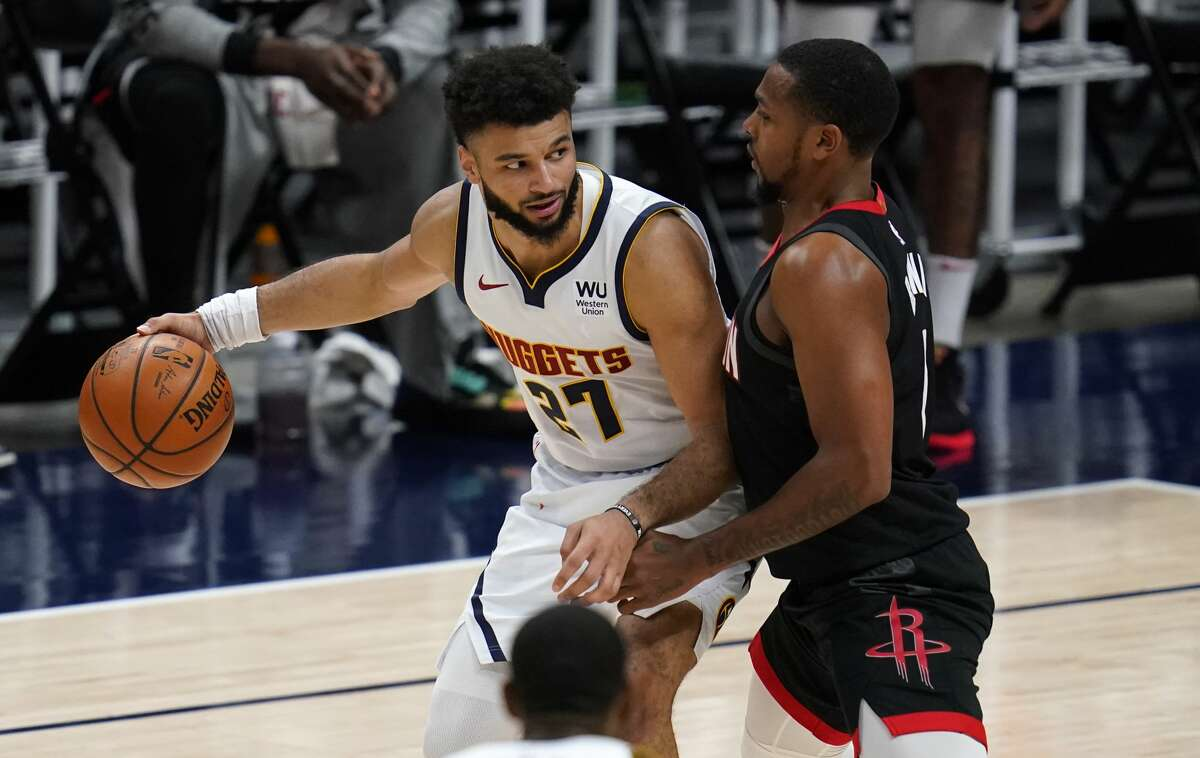 Denver Nuggets guard Jamal Murray, left, looks to pass the ball as Houston Rockets guard Sterling Brown defends during the second half of an NBA basketball game Monday, Dec. 28, 2020, in Denver. The Nuggets won 124-111. (AP Photo/David Zalubowski)