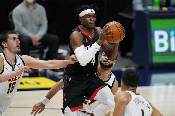 Houston Rockets forward Danuel House Jr., center right, drives to the net while surrounded by, Denver Nuggets center Nikola Jokic, left, guard Jamal Murray, back, and forward Michael Porter Jr. in the second half of an NBA basketball game Monday, Dec. 28, 2020, in Denver. (AP Photo/David Zalubowski)