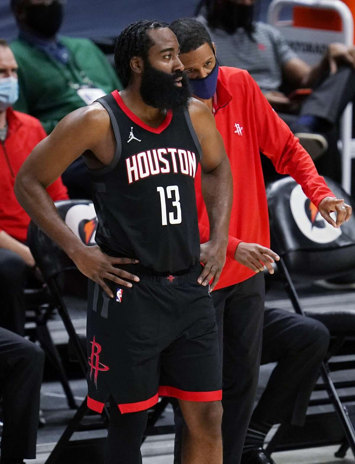 Houston Rockets guard James Harden confers with coach Stephen Silas during the second half of the team's NBA basketball game against the Denver Nuggets on Monday, Dec. 28, 2020, in Denver. (AP Photo/David Zalubowski)