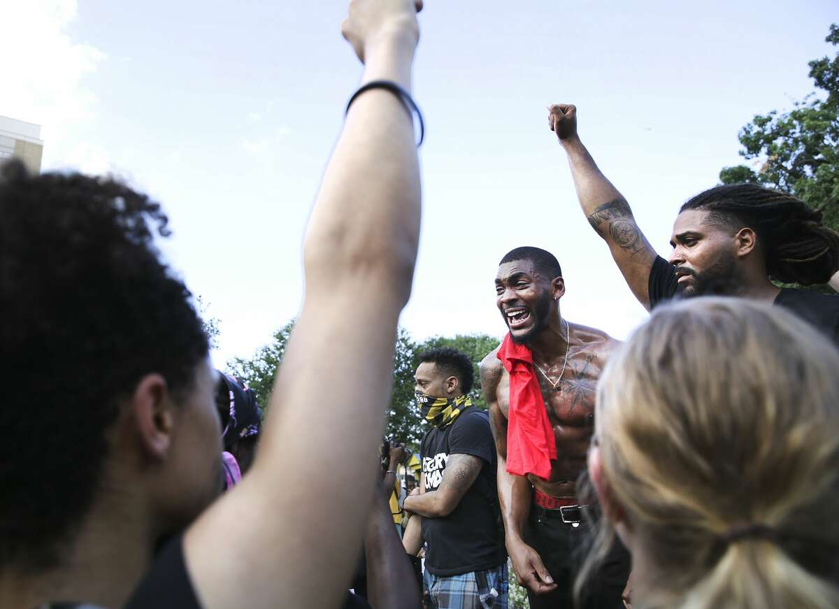 "Trevor Taylor, center, cries as he explains how he felt after lying in the grass yelling ""I can't breathe!"" as protestors marched to Travis Park, on Wednesday, June, 3, 2020."