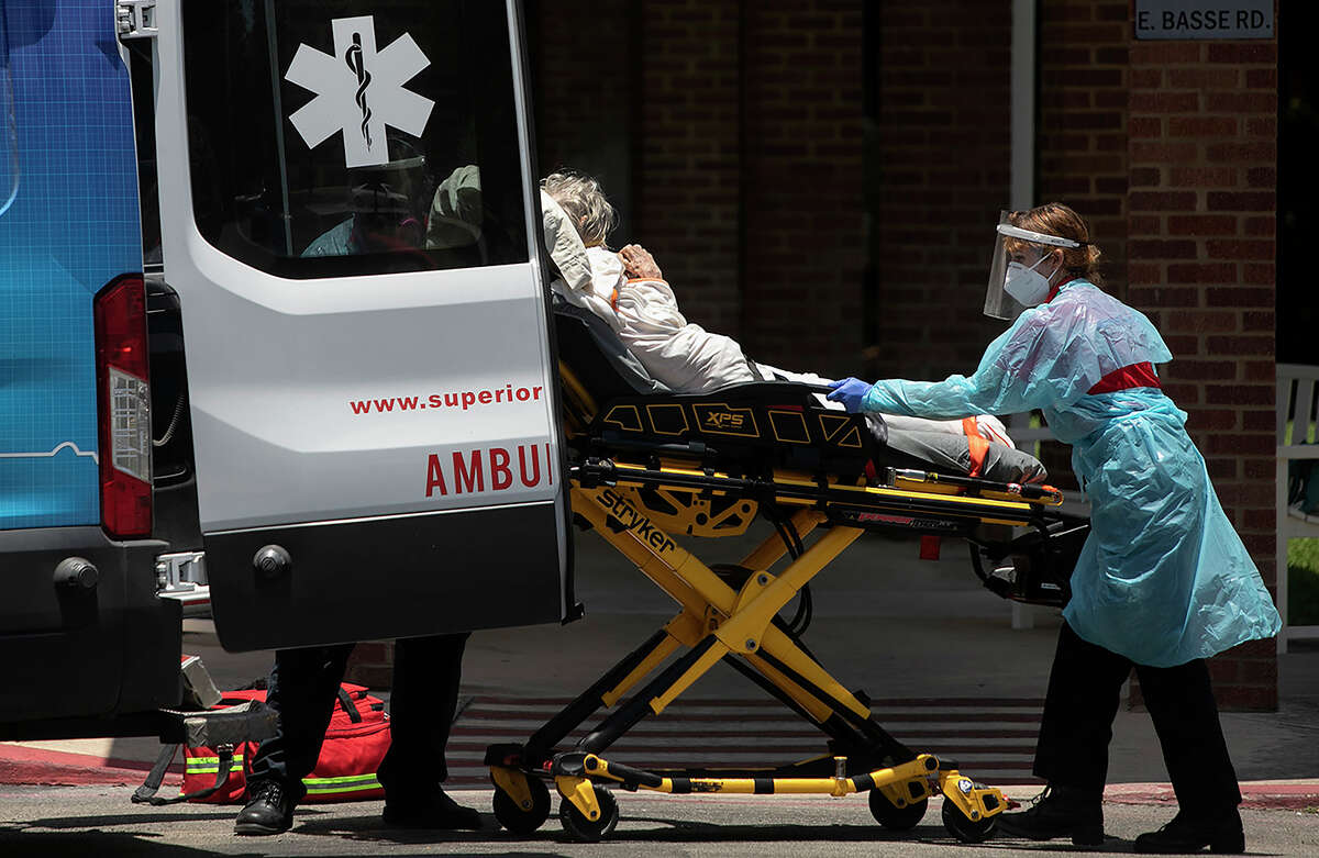 Superior Mobile Health paramedics George Lombardo and Katheryn Wieding, right, transport a woman they were told was COVID-19 positive from an assisted living facility to a hospital on July 14, 2020 in San Antonio.