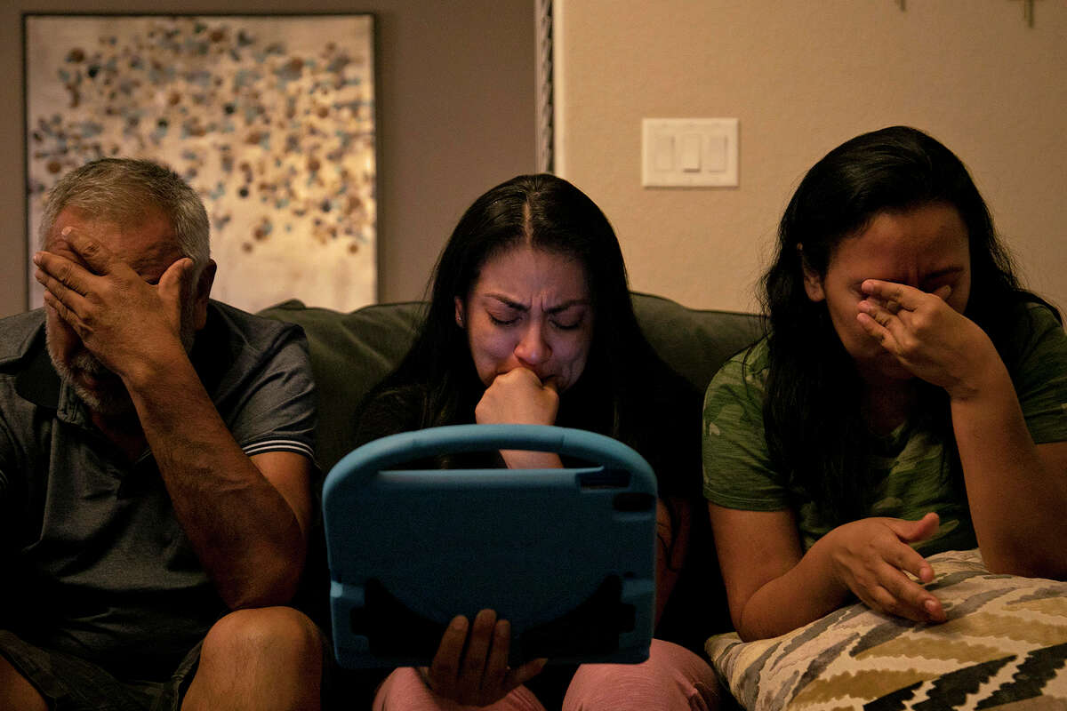 """Vanessa Dyer, center, her sister, Alex Vasquez, and their father, Enrique Rangel, are brought to tears as their brother, Andy Rangel, at his home speaking to their mother, Leonor """"Nora"""" Rangel, who was on a ventilator at Southwest General Hospital, through FaceTime, tells her if she is tired it is okay to go, at Dyer's home in San Antonio. The siblings and other family members FaceTimed with their mother every night as she fought COVID-19, with the help of nurses setting up an iPad next to her bed. After 40 days with symptoms, 37 days in the hospital and 17 on a ventilator, 63-year-old Leonor """"Nora"""" Rangel, of Del Rio, passed peacefully at Southwest General Hospital in San Antonio on July 26, 2020."""