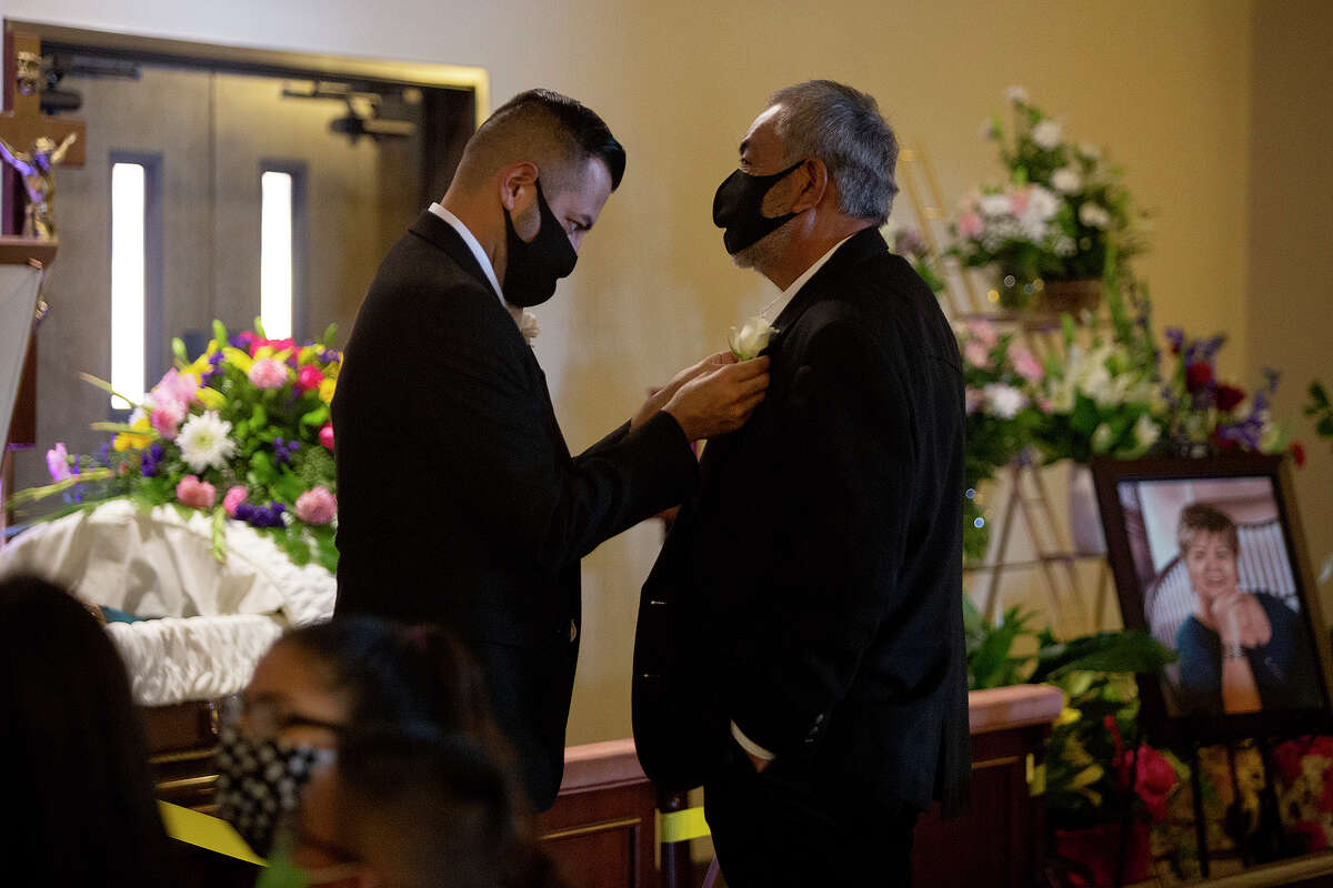 """Andy Rangel pins a flower for his father, Enrique Rangel, before the funeral mass and burial of Andy's mother and Enrique's wife, Leonor """"Nora"""" Rangel, in photo at right, in Del Rio on Saturday, August 1, 2020."""