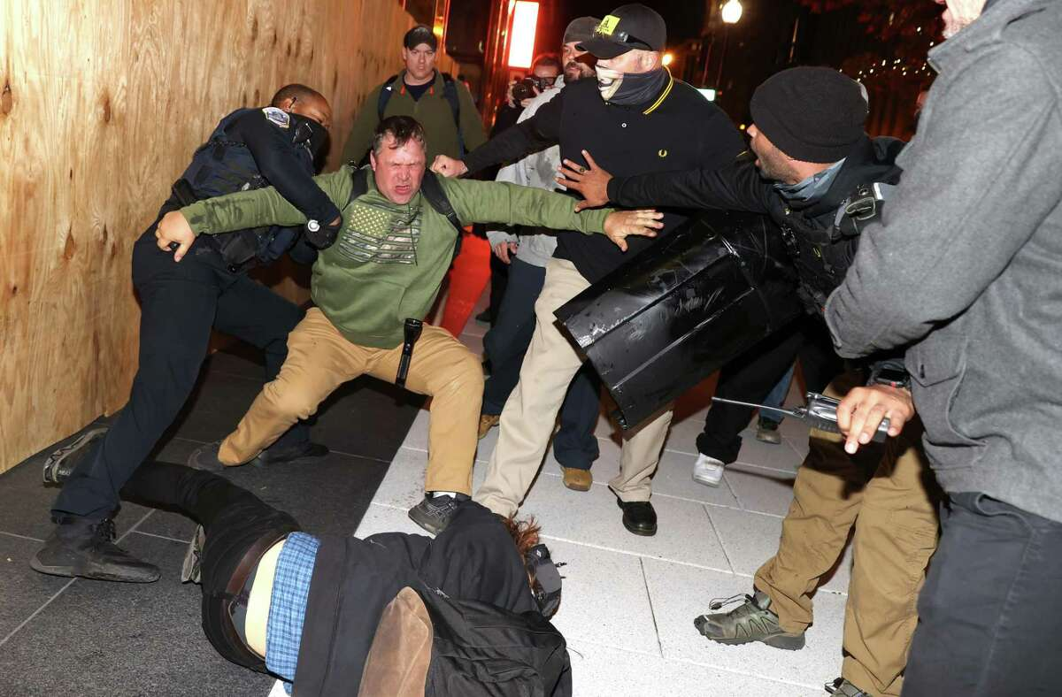 A police officer tries to break up a fight between Black Lives Matter protesters and members of the Proud Boys during a protest following the