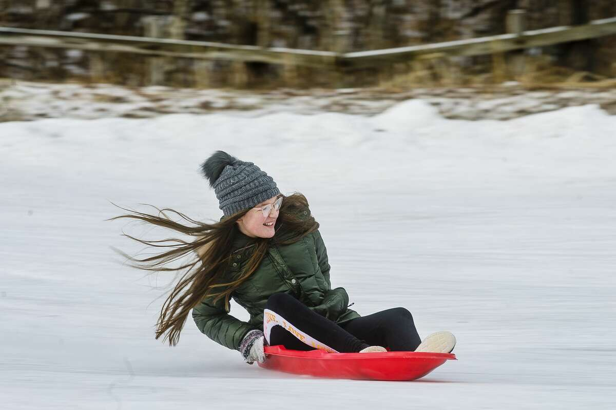 Celie Periard, 11, tries to keep her balance as she speeds down the sledding hill Monday, Dec. 28, 2020 at City Forest in Midland. (Katy Kildee/kkildee@mdn.net)