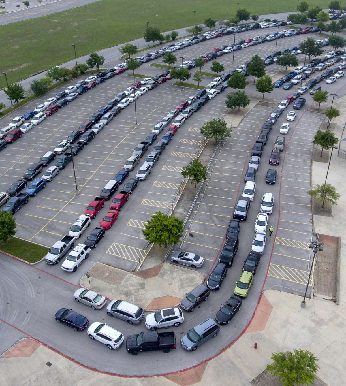 Vehicles queue Tuesday, April 7, 2020, in the Heroes Stadium parking lot to receive food aid from the Food Bank. Demand for food aid has skyrocketed since the the start of the COVID-19 coronavirus pandemic.
