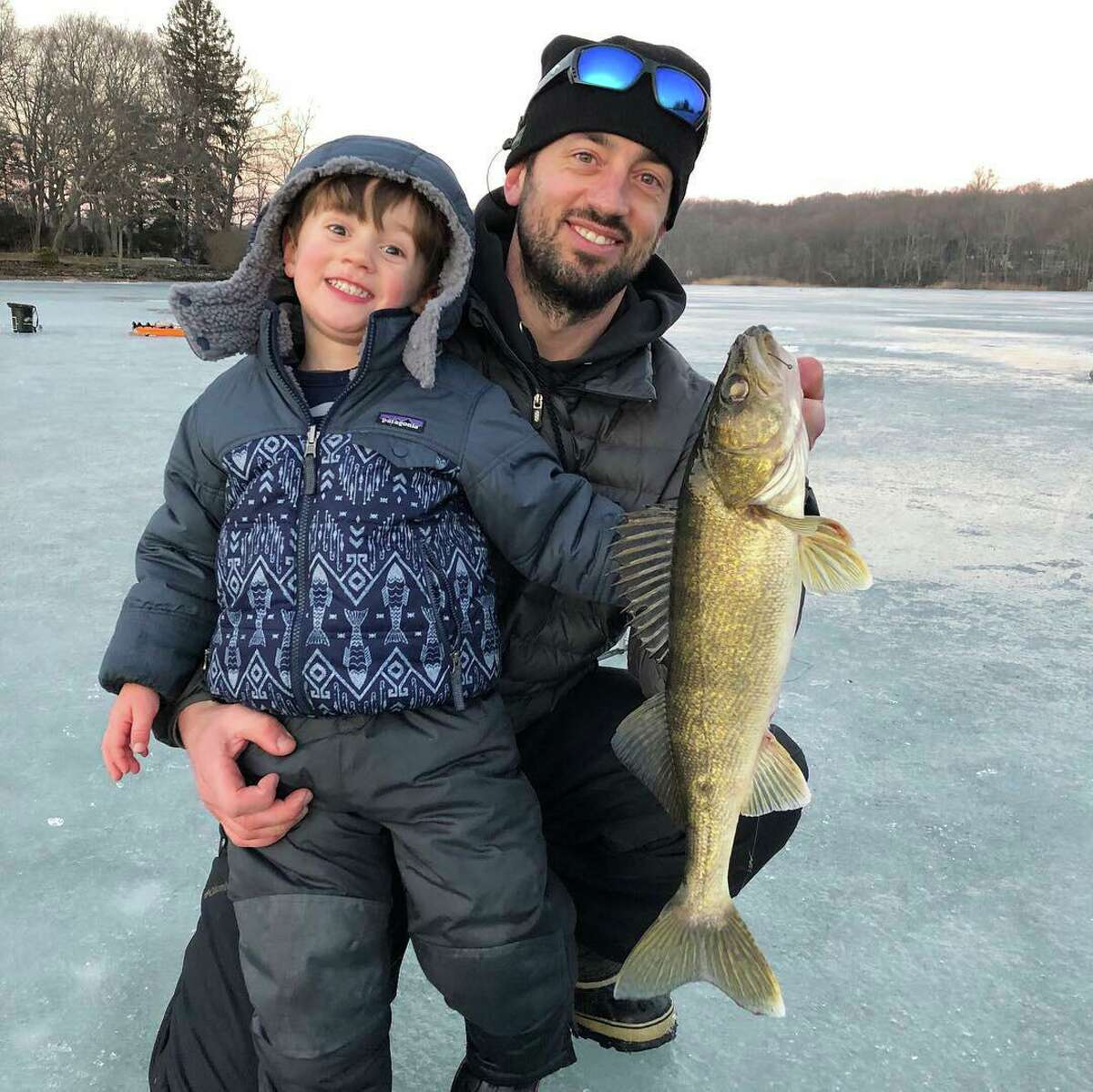 Justin Wiggins and his son, Quinn, show off a keeper walleye last February while enjoying ice fishing at Coventry Lake. Wiggins coordinates the fishing education program for Connecticut's Department of Energy and Environmental Protection.