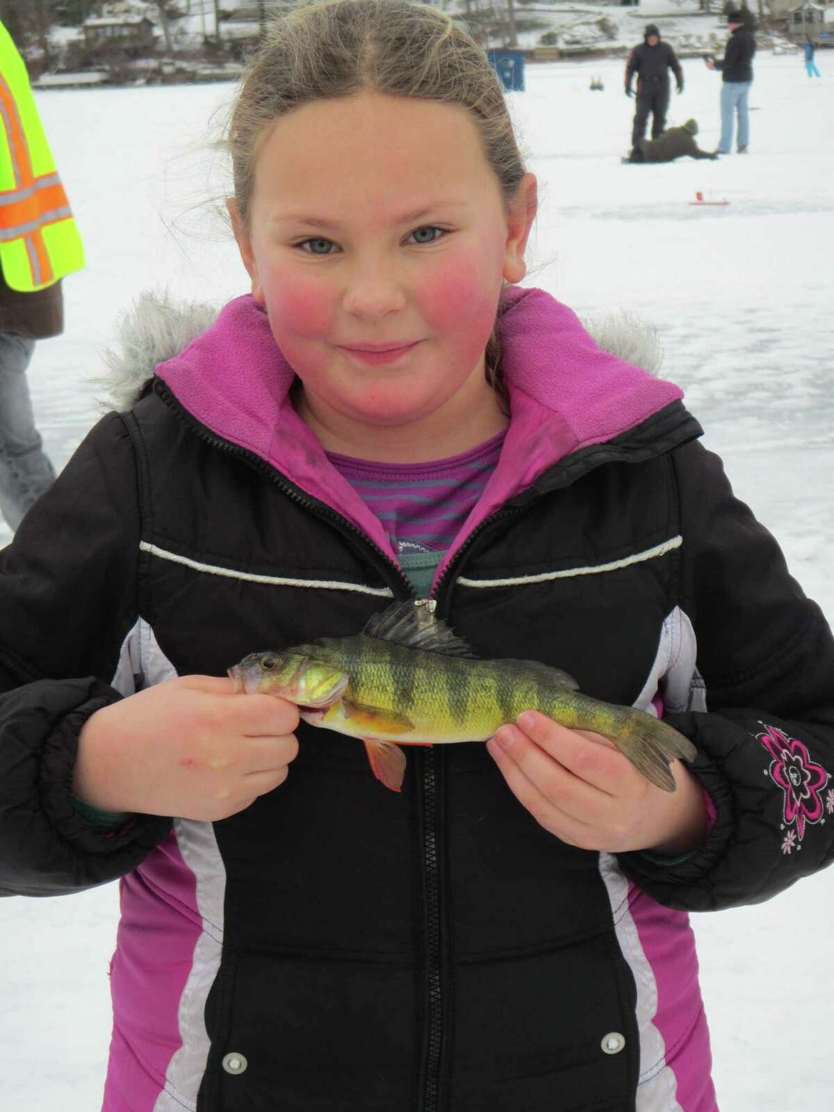 A rosy-cheeked ice angler shows off what she caught during an ice fishing event held by Connecticut's Department of Energy and Environmental Protection.
