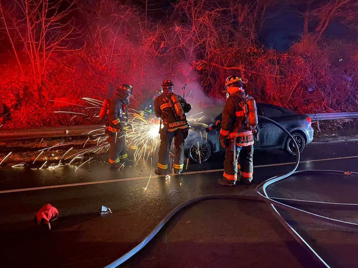 Firefighters use gas-powered saws to access the engine of a vehicle after extinguishing flames to make sure the fire was fully out, and to investigate the cause and origin.