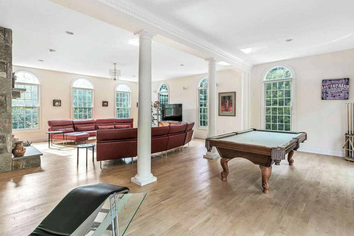 A portion of the family room was converted into a game room at 166 Wells Hill Road, Easton. This residential property also straddles both towns. While the address is in Easton and any children who live there would matriculate in Easton's public schools, there is a small portion of the property that crosses into Weston. Its homeowners pay taxes to both municipalities. The 14-room house, which was built in 1999 with 6,314 square feet of living and entertaining space, is only one of this property's many assets. In 2006 they built the red storage barn and the 20-by-40-foot heated in-ground swimming pool. The barn contains a heated workshop and two vehicle bays. It was